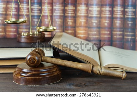 Wood gavel, soundblock, scales and open old book against the background of a row of antique books bound in leather - stock photo