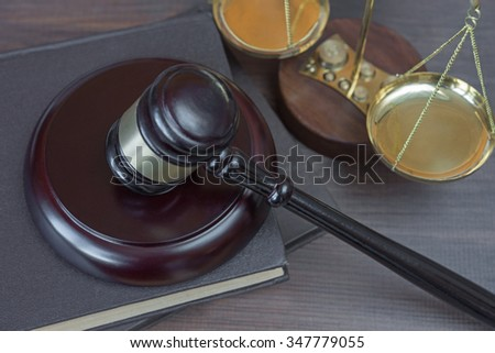 Wood gavel, soundblock, scales and stack of old books bound in leather on the wooden background - stock photo