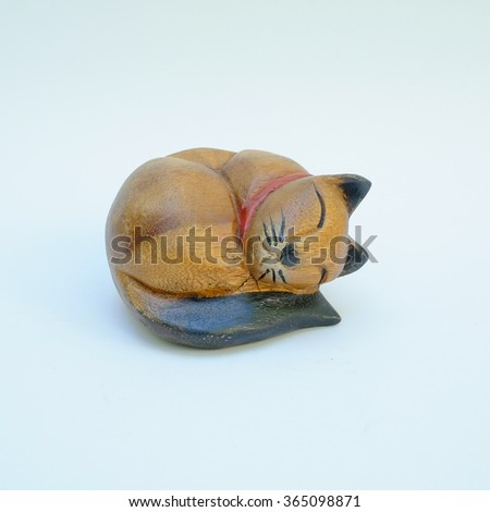 wood handcrafted sleeping cat on the book - stock photo