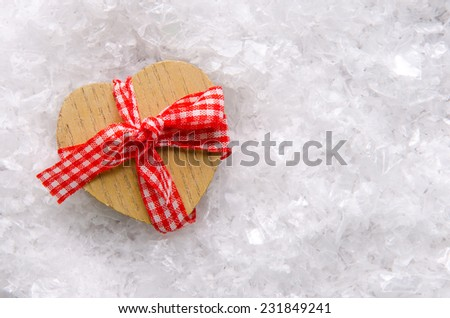Wood heart decoration with bow on artificial snow. - stock photo