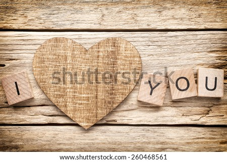 Wood heart on old wooden background - Stock Image. I love you, cast out of wood kubik. - stock photo