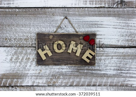 Wood HOME sign with red hearts hanging on antique rustic white wooden background; family and love concept - stock photo