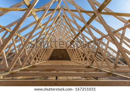 Wood house truss against blue sky  - stock photo