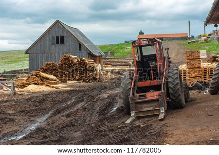 Wood industry outdoors with red tractor
