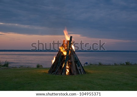 Wood is stacked and the  fire started for evening  bonfire - stock photo