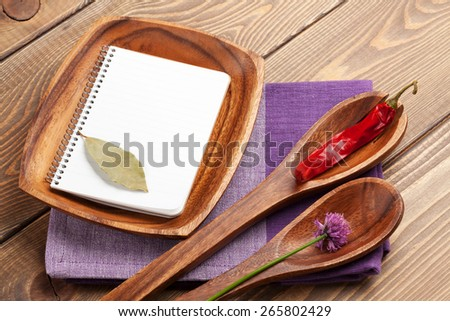 Wood kitchen utensils and spices over wooden table background with notepad for copy space - stock photo