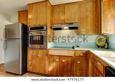 Wood kitchen with blue tiles and stainless steal appliances.