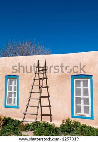 Wood ladder against adobe wall.