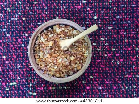wood ladle sugar, rock sugar and wood ladle on fabric background, vintage color - stock photo