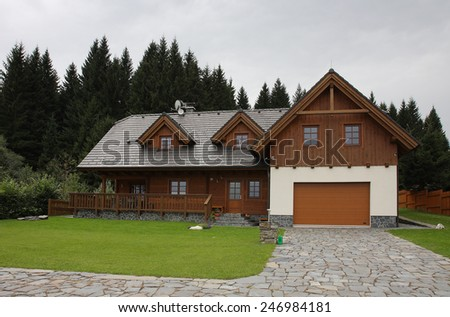 Wood log cabin near forest in cloudy day - stock photo