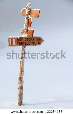 Wood made directional sign on a mountain trail during winter - stock photo