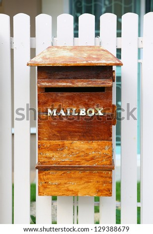 Wood mailbox against white fence - stock photo