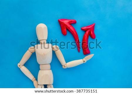 wood man in doubt, having to shoose between two different choices indicated by arrows pointing in opposite direction concept - stock photo