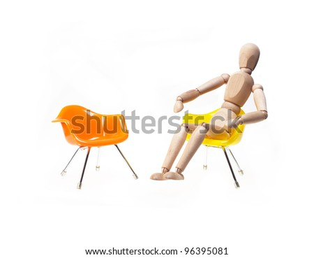 wood mannekin waiting for meeting sitting on chair over white - stock photo