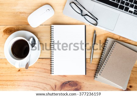 Wood office desk table with a lot of things on it. Top view. Blank notebook page in the middle can be put some texts or images. - stock photo
