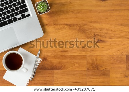 Wood office desk table with laptop, coffee, paper and pen. Top view with copy space. - stock photo