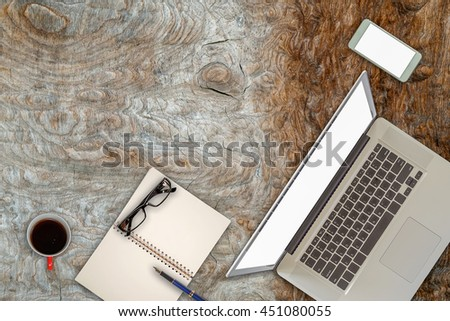 Wood office desk with laptop, coffee, mobile phone and pen. Top view with copy space.