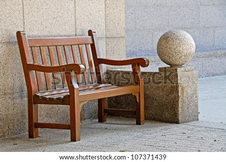 Wood Park Bench against Stone Wall - stock photo