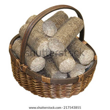 Wood pellets arranged in a wicker basket, isolated on white background - stock photo