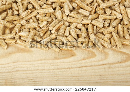 wood pellets on wood with copy space - stock photo