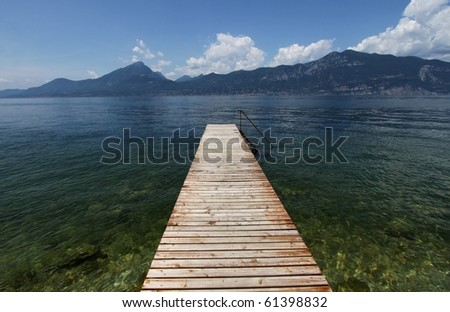 Wood pier on the Garda Lake in North Italy - stock photo