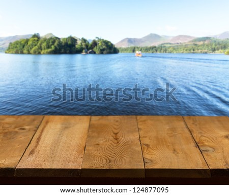 Wood pier or walkway or an old wooden table with blurred image of lake district in England as background - stock photo