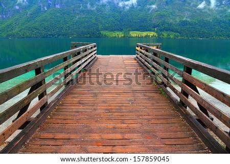 Wood pier over mountain lake water - stock photo