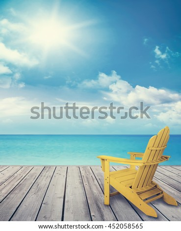 Wood pier with sun chair and ocean in background - stock photo