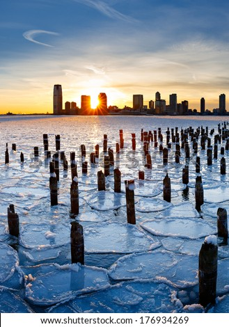 Wood pilings from New York old pier sticking out through the ice on Hudson River at sunset with Jersey City buildings in the distance. Frozen Hudson River January 2014. - stock photo