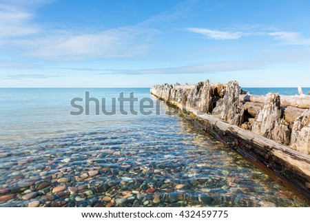 Wood Pilings jut out into Lake Superior at Whitefish Point in the Upper Peninsula of Michigan. Clear lake water reveals the colorful stones under the water - stock photo
