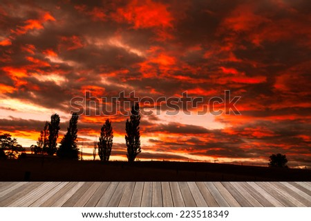 wood plank platform on silhouette prairie with awesome morning sky