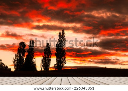 wood plank platform on silhouette prairie with awesome morning sky - stock photo