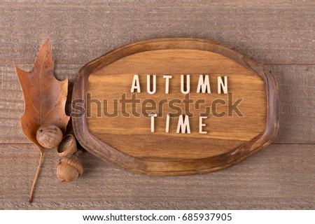 Wood plaque with autumn time text with oak leaf and acorns