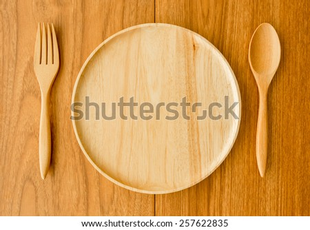 Wood plate fork spoon with window light from left side - stock photo