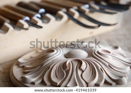 Wood processing. Joinery work. wood carving. the carving object with pattern, chisels for carving close up. small depth of field. retro style filter. use as background - stock photo