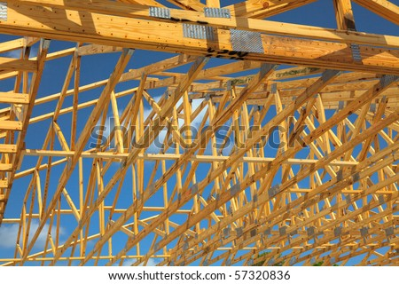Wood Roof Trusses viewed from inside of new home looking out to a blue sky above - stock photo