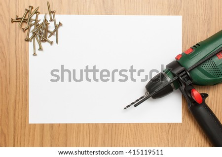 Wood screw and electric drill on white and wooden background. - stock photo