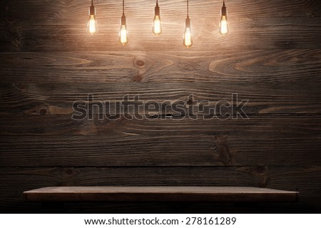 Wood shelf, grunge industrial interior with edison light bulb - stock photo