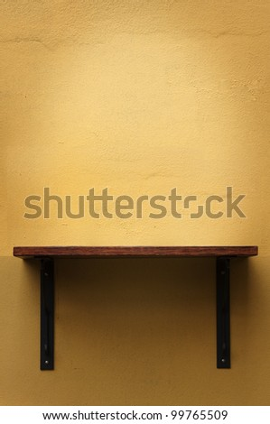 Wood shelf on yellow wall - stock photo