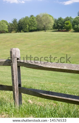 Wood Split Rail Fence with Grassy Landscape Background - stock photo