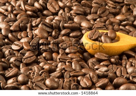 Wood spoon and coffee grains - stock photo
