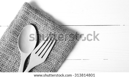 wood spoon and fork on kitchen towel over background black and white tone color style