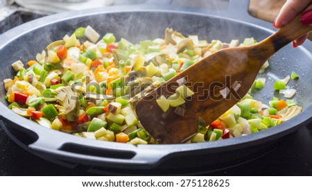 Wood spoon mixing Mediterranean veggies on a pan