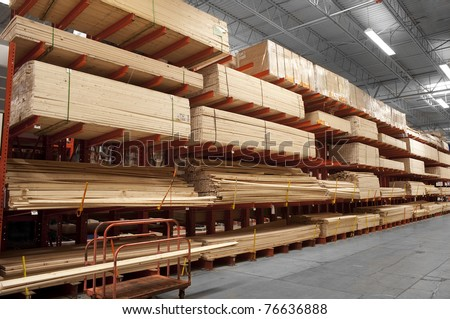 Wood stacked on shelving inside a lumber yard - stock photo