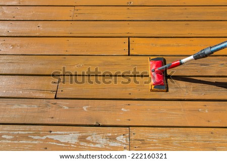 Wood stain with a paint pad  on wooden deck floor. - stock photo