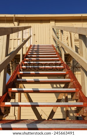 Wood stairs going up to a rescuer beach house  - stock photo