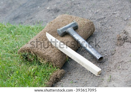 Wood stick and hammer tool for fixing rolled sod grass turf on soil and erosion control mesh during lawn reseeding - stock photo