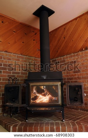 Wood Stove on red brick with the metal doors open letting heat warm up the room in a lodge.
