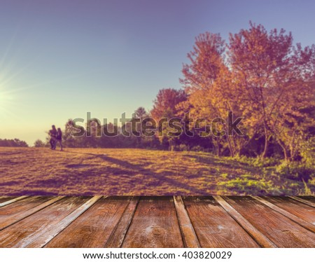 wood table and blur silhouette vintage tone image of group of people in sunrise time with mountain and sun in background. - stock photo