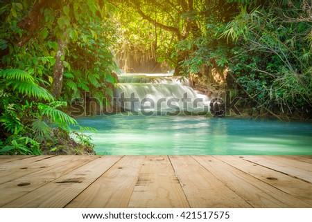 Wood table and Kuang Si waterfalls in Luang Prabang, Laos. - stock photo